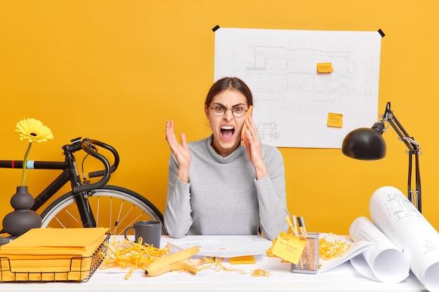 Foto van boze vrouwelijke kantoormedewerker heeft telefoongesprek roept met verontwaardigde uitdrukking eist hulp poses in coworking space werkt aan nieuw creatief project maakt blauwdrukken. baan concept