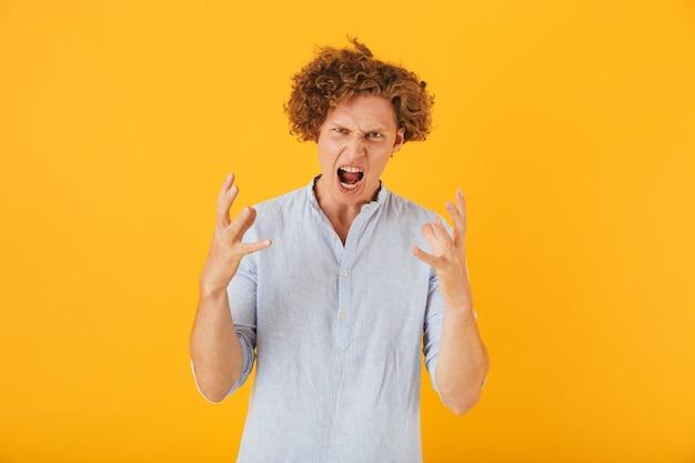 Foto van boze woedende man met krulhaar verhogen handen in irritatie, geïsoleerd op gele achtergrond