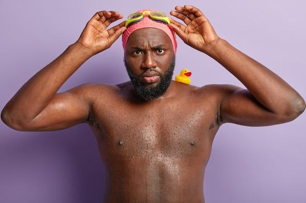 Foto van boze zwarte man past bril aan, ziet er somber uit, gaat naar sportgedeelte, zwemt heel goed, heeft rubberen speelgoed eendje op schouder, komt uit water heeft natte huid, kijkt ontevreden