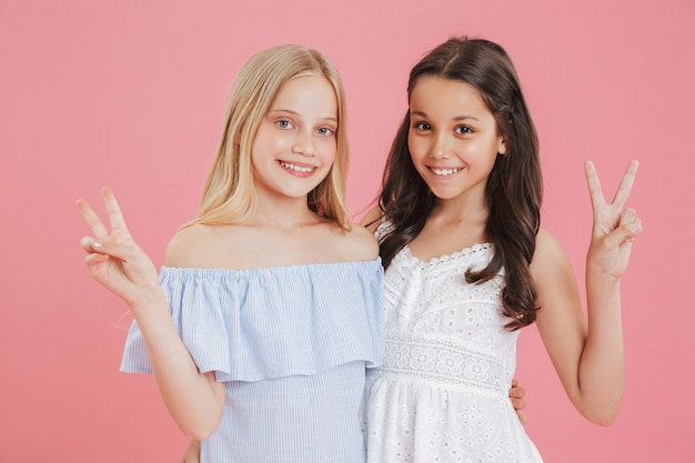 Foto van brunette en blonde prinsesmeisjes die jurken dragen die en vredesteken glimlachen tonen.