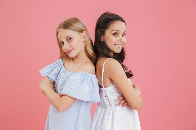 Foto van brunette en blonde schattige meisjes die jurken dragen die glimlachen en kijken terwijl ze rug aan rug met gevouwen armen staan.