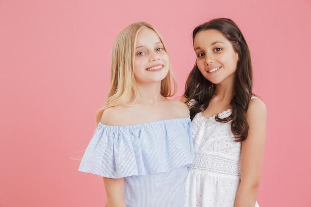 Foto van brunette en blonde schattige meisjes dragen jurken glimlachend en kijken.