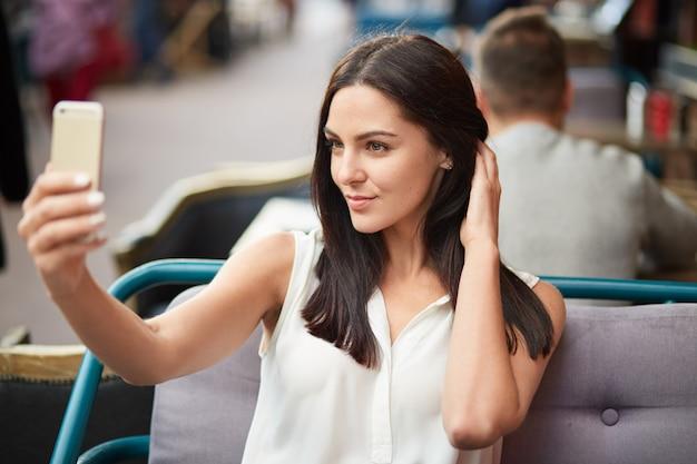 Foto van brunette jonge dame neemt selfie met moderne mobiele telefoon, gekleed in witte blouse, maakt foto- of videogesprek, geniet van haar uiterlijk