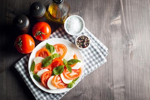 Foto van caprese salade met tomaten, basilicum, mozzarella, olijven en olijfolie