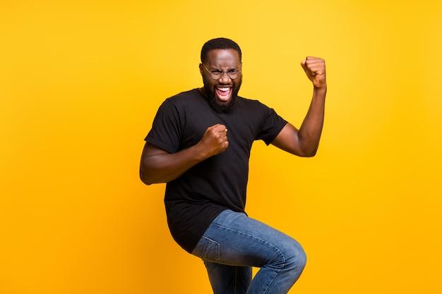 Foto van casual opgewonden gekke extatische man donkerbruin haren in spijkerbroek denim t-shirt vreugde in het kopen van een nieuwe bril geïsoleerde levendige kleurenmuur