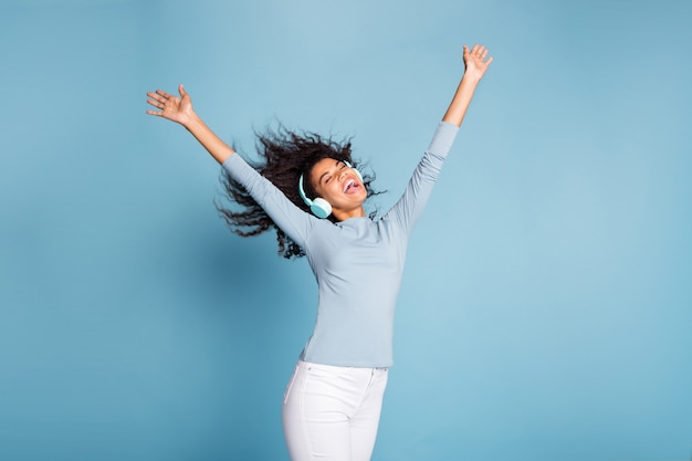 Foto van casual vrolijke positieve leuke mooie vriendin in witte broek met haar gegooid bruine haren geïsoleerde pastel blauwe kleur achtergrond