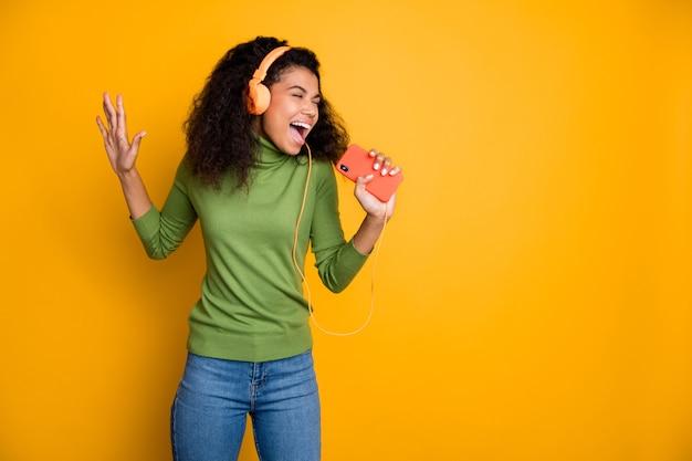 Foto van casual vrolijke vrij mooie jongere die in de telefoon zingt en zich voorstelt dat het micriphone schreeuwt in spijkerbroek denim geïsoleerde gele levendige kleurenachtergrond