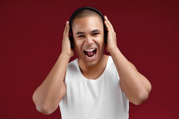 Foto van charismatische emotionele gemengde race man die lol heeft, naar muziek luistert in een zwarte koptelefoon, positiviteit uitdrukt en schreeuwt terwijl hij meezingen met favoriete nummers, zich vrolijk voelt