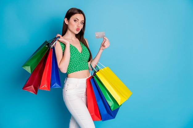 Foto van charmant prachtig meisje houdt man tassen creditcard stuur lucht kus draag groene gestippelde hemd witte broek broek geïsoleerd over blauwe kleur achtergrond