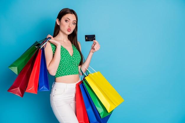 Foto van charmant, prachtig meisje, stuur luchtkus, houd veel tassen, creditcard, draag witte broek, broek, groene gestippelde tanktop geïsoleerd over blauwe achtergrondkleur