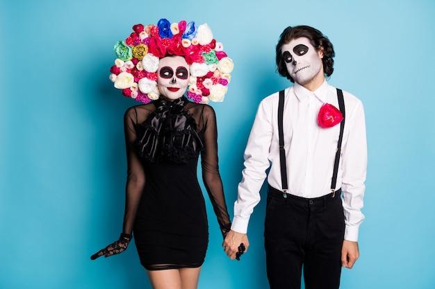 Foto van charmant spookachtig paar man dame verlegen blik blozen eerste date na de dood hand in hand dragen zwarte mini korte jurk dood kostuum rozen hoofdband bretels geïsoleerde blauwe kleur achtergrond