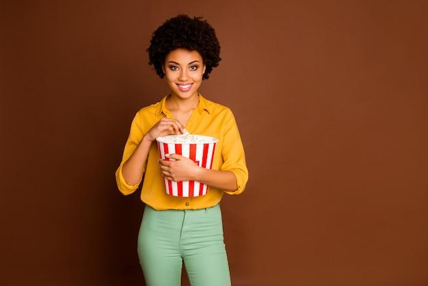 Foto van charmante donkere huid golvende dame met popcorn emmer eet likdoorns kijken naar favoriete tv-show dragen gele shirt groene broek geïsoleerde bruine kleur