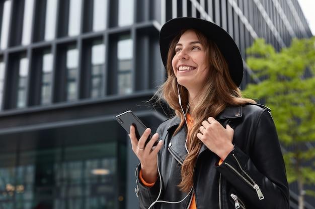 Foto van charmante dromerige vrouw houdt moderne cellulaire, luistert muziek tijdens wandeling buiten in metropool
