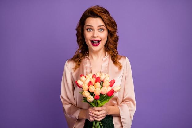 Foto van charmante gekke dame die een bos verse tulpenbloemen vasthoudt