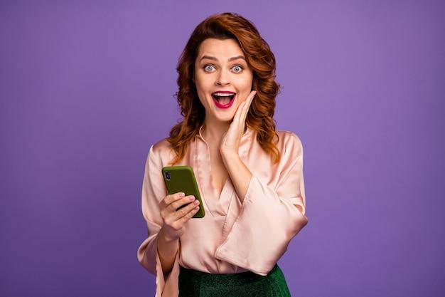 Foto van charmante gekke dame houdt telefoon met open mond hand op jukbeen