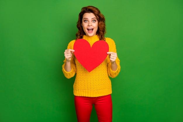 Foto van charmante golvende opgewonden dame houden papier hartvorm briefkaart vriendje uitnodiging voor romantiek date slijtage gele gebreide trui rode broek geïsoleerd helder groene kleur muur