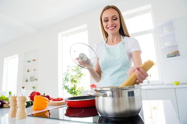 Foto van charmante huisvrouw genieten van weekendochtend koken lekker diner houden spaghetti zetten kokend water stand wit licht keuken binnenshuis
