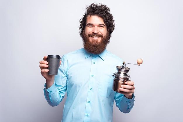 Foto van charmante jonge bebaarde man in casual bedrijf kopje koffie meenemen en handmatige koffiemolen.
