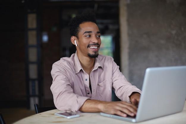 Foto van charmante jonge donkere man met kort kapsel aan tafel zitten en handen houden op het toetsenbord van zijn laptop, grappige grap horen en vreugdevol glimlachen