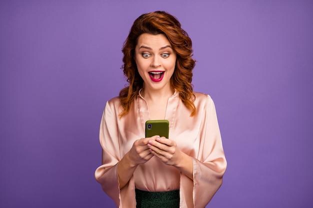 Foto van charmante mooie foxy dame houdt telefoon met open mond dolblij