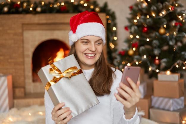 Foto van charmante schattig mooi aantrekkelijk meisje haar telefoon en geschenkdoos in handen houden