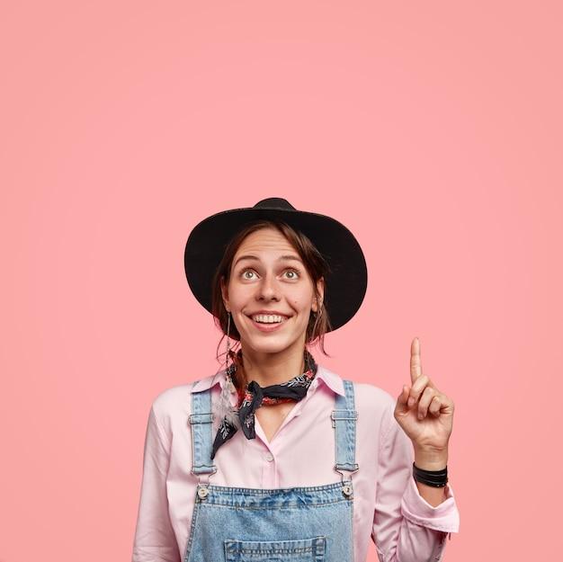 Foto van charmante tedere vrouw glimlacht positief, kijkt vreugdevol naar boven, wijst met wijsvinger