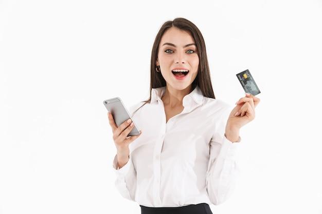 Foto van charmante vrouwelijke werkneemster, gekleed in formele kleding met smartphone en creditcard terwijl ze op kantoor werkt, geïsoleerd over een witte muur