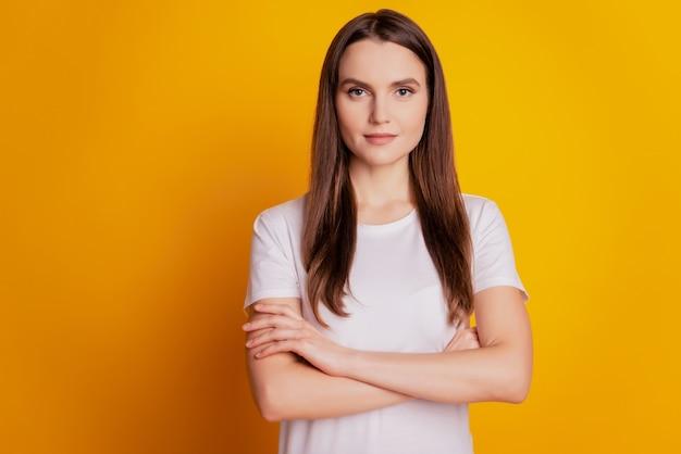 Foto van charmante zelfverzekerde dame met gekruiste handen draagt een wit t-shirt poserend op een gele achtergrond