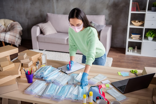 Foto van chinese drukke dame armen latex handschoenen organiseren bestelling gezicht griepmaskers voorbereiden levering anti-virale veilige controle ademhalingstoestellen in rits zak nota klembord staat thuiskantoor binnenshuis