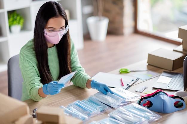 Foto van chinese drukke dame familiebedrijf organiseren verpakking gezicht griep medische maskers wereldwijde verspreiding doneren arme landen sets voorbereiden voor levering thuiskantoor quarantaine binnenshuis