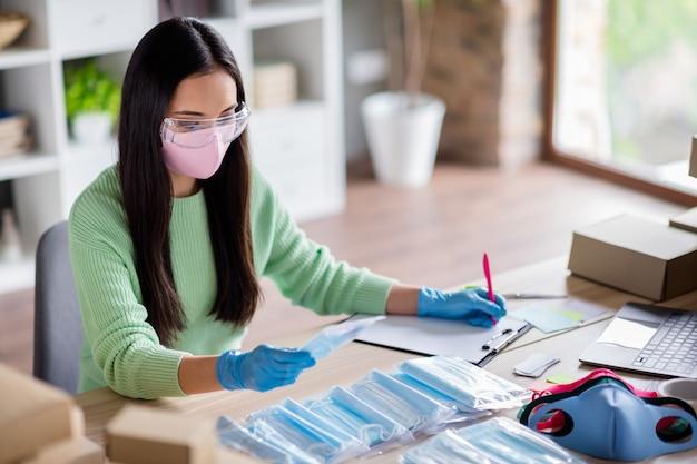 Foto van chinese drukke dame familiebedrijf organiseren verpakking gezicht griep medische maskers wereldwijde verspreiding schrijfbestelling details voorbereiden van sets voor levering thuiskantoor quarantaine binnenshuis