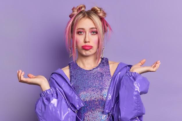 Foto van clueless jonge europese vrouw ziet er helaas uit heeft twee haarbroodjes spreidt handpalmen gezichten moeilijke keuze