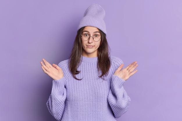 Foto van clueless millennial meisje met lang donker haar spreidt handpalmen en. Gratis Foto