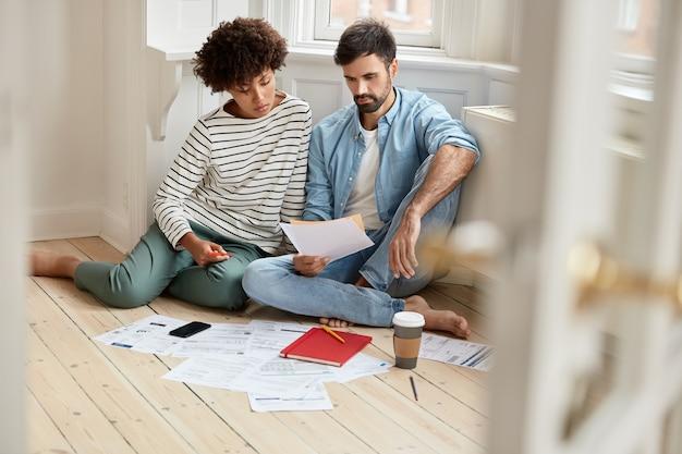 Foto van collega's van gemengd ras bestuderen financiële rekeningen, dragen comfortabele kleding, poseren op de vloer, bespreken toekomstig werk en samenwerking, omringd met documenten, koffie en mobiel. werkend concept