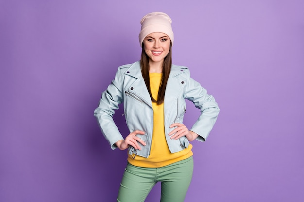 Foto van cool stijlvol goed humeur mooie dame warme lente weer dag straat kleding glimlachende handen aan de zijkanten dragen casual hoed blauwe moderne stijl jas broek geïsoleerde paarse kleur achtergrond