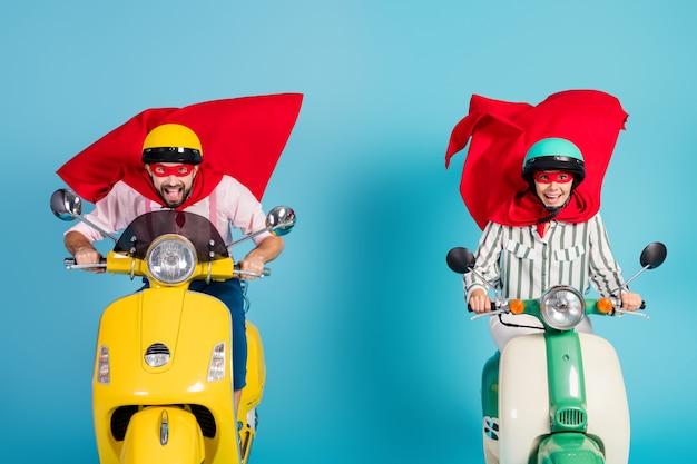 Foto van coole dame man rijden rit twee retro bromfiets dragen rode cape masker beschermende hoeden haasten weg halloween feest spelen superhelden rol jas vliegen lucht geïsoleerde blauwe kleur muur