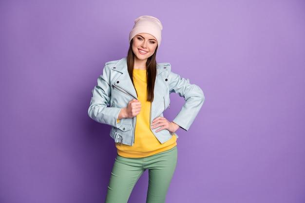 Foto van coole stijlvolle aantrekkelijke dame warm lenteweer mooie dag straatkleren glimlachend stralend goed humeur draag casual hoed blauwe moderne stijl jas broek geïsoleerde paarse kleur achtergrond