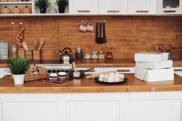 Foto van cupcakes, marshmellows, witte dozen met snoep op de kast
