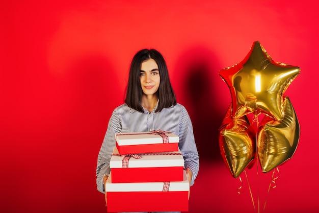 Foto van dame die drie grote geschenkdozen en drie gouden luchtballons houdt die over rode kleurenachtergrond worden geïsoleerd. verjaardagsfeest.
