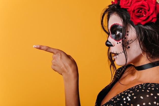 Foto van dame in zwarte top in profiel. verrast meisje met schedelmake-up toont vinger aan kant