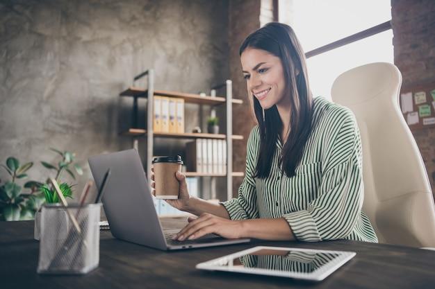 Foto van dame secretaris zitten bureau houden koffiekopje e-mail typen op netbook op kantoor