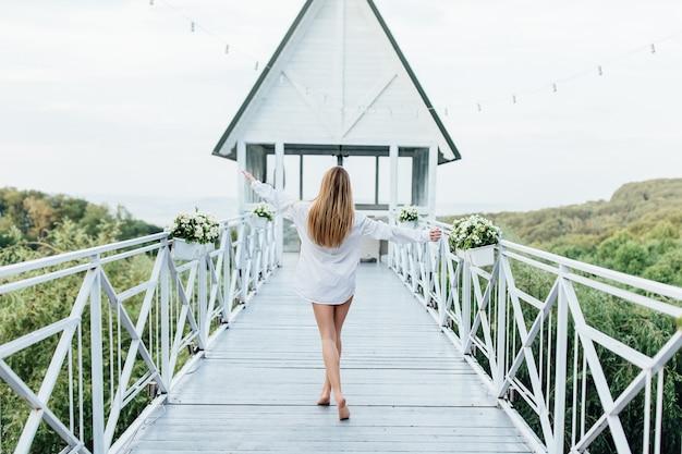 Foto van de achterkant. ochtend van de bruid, aantrekkelijk meisje in het shirt van een man op het zomerterras.