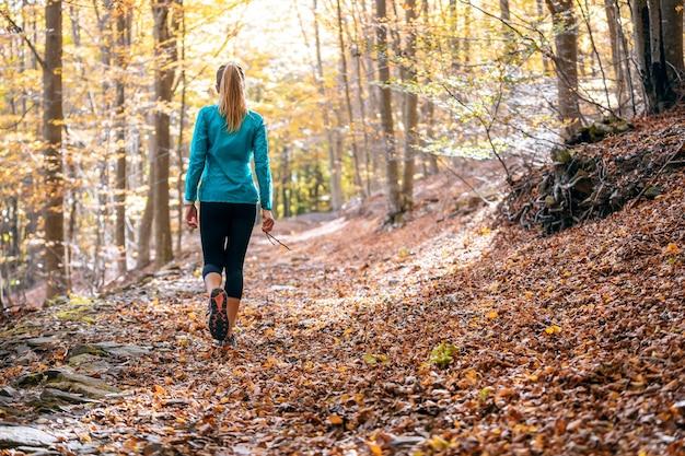 Foto van de achterkant van een sportieve jonge vrouw die in de herfstochtend in het park loopt.