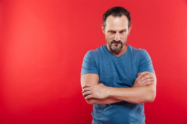 Foto van de agressieve mens die toevallige t-shirt draagt die zich met gekruiste handen bevindt en op camera met boze blik kijkt, die over rode achtergrond wordt geïsoleerd