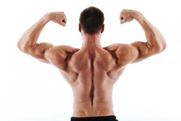 Foto van de atletische jonge mens die zijn rug en bicepsspieren toont