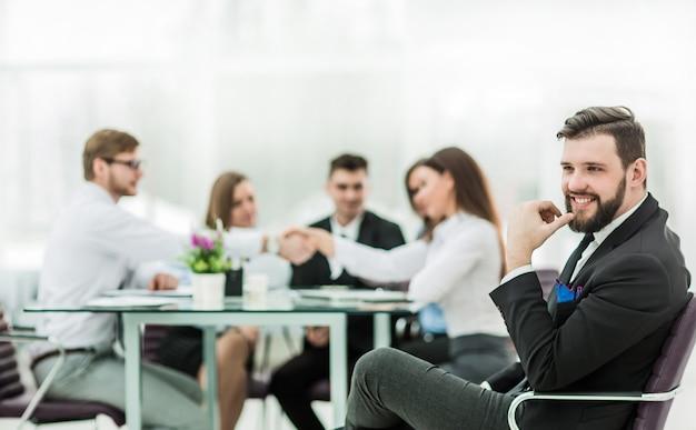 Foto van de baas op de achtergrond van de handdruk van een manager met een klant op de werkplek in een modern kantoor. de foto heeft een lege ruimte voor uw tekst