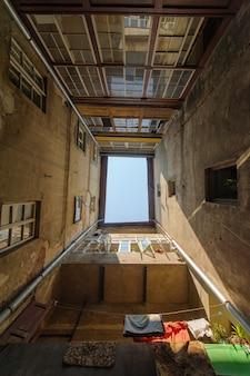 Foto van de binnenplaats waar de huizen in de vorm van een vierkant staan. kijk naar de hemel. de arme oude wijk van de stad.