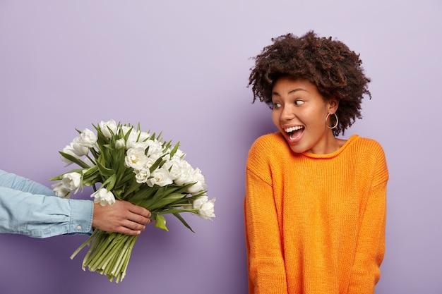 Foto van de blije afro-amerikaanse jonge vrouw kijkt gelukkig naar boeket bloemen dat de man vasthoudt