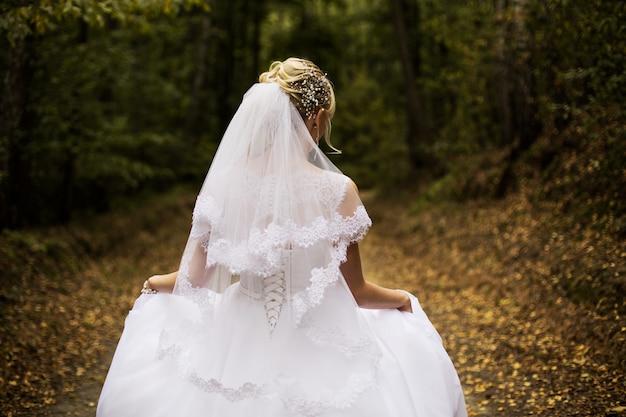 Foto van de bruid vanaf de achterkant, trouwjurk op een meisje, de bruid in het bos,