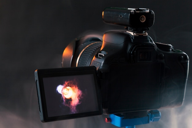 Foto van de camera op een blauw statief dat in de studio een professioneel verlichtingsapparaat in de rook fotografeert. studio verlichting en rookapparatuur. reclame fotosessie van het verlichtingsapparaat